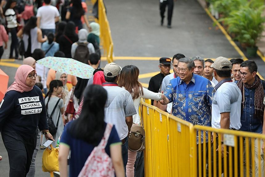 Former Indonesian president Susilo Bambang Yudhoyono arriving at Singapore's Indonesian embassy yesterday for early voting. He stole the limelight when he turned up in the evening, drawing squeals and handshakes.