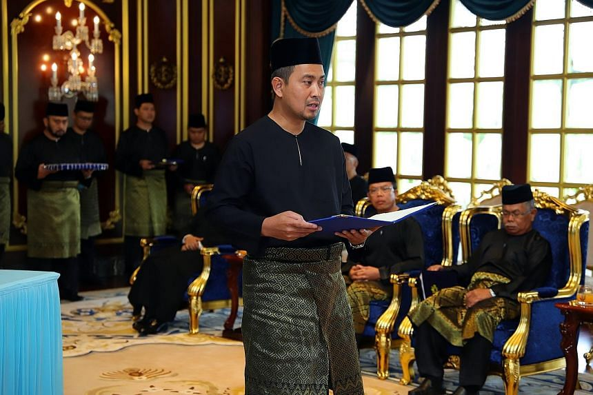 Dr Sahruddin Jamal being sworn in as Johor's 17th Menteri Besar yesterday at the main state palace, Istana Bukit Serene. The 43-year-old replaces Datuk Osman Sapian.