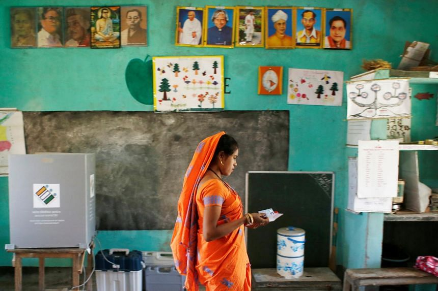 A woman leaves after casting her vote at a polling station during the first phase of general election in Majuli, India, on April 11, 2019.