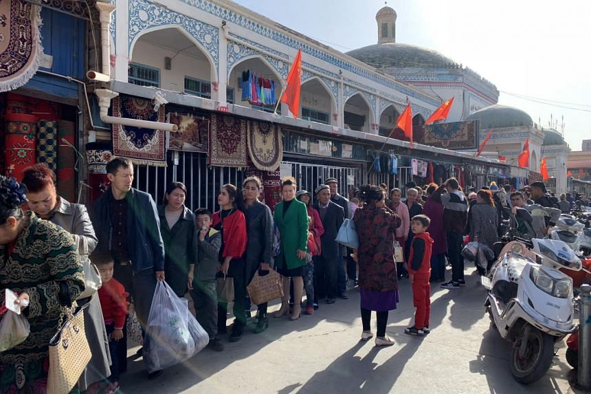 Shoppers line up for identification checks outside the Kashgar Bazaar in China's Xinjiang region, on Oct 21, 2018.