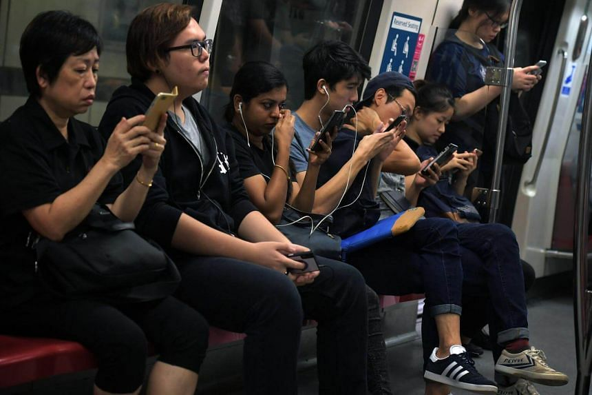 Commuters looking at their phones on an MRT train.