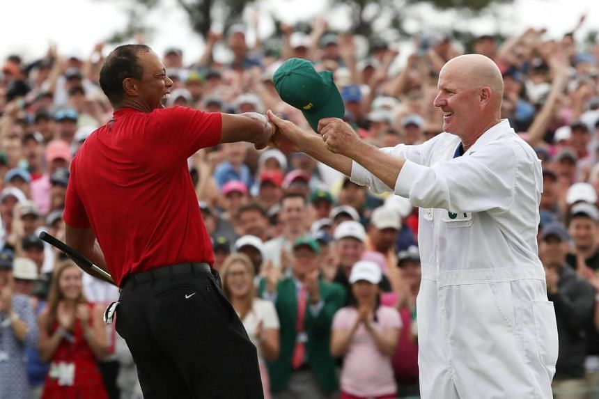 Tiger Woods celebrates with caddie Joe LaCava on the 18th hole of the 2019 Masters at Augusta National Golf Club, on April 14, 2019.