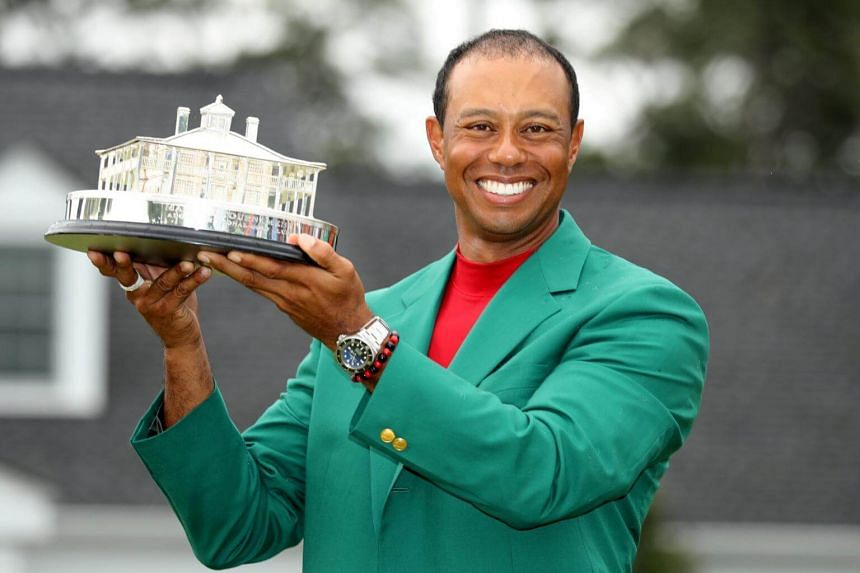 Tiger Woods celebrates with his green jacket and trophy after winning the 2019 Masters.