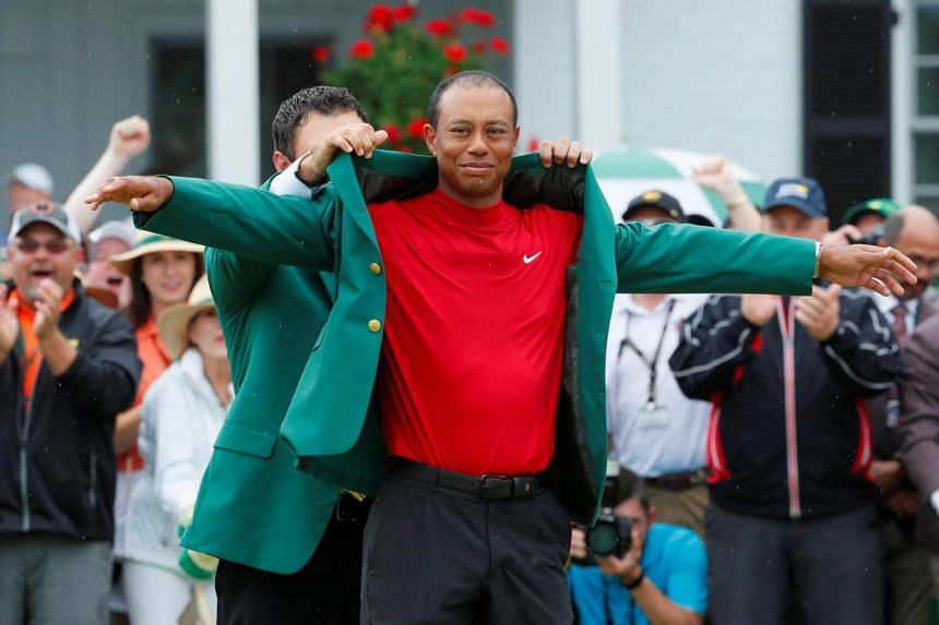 Patrick Reed places the green jacket on Tiger Woods after Woods won the 2019 Masters.