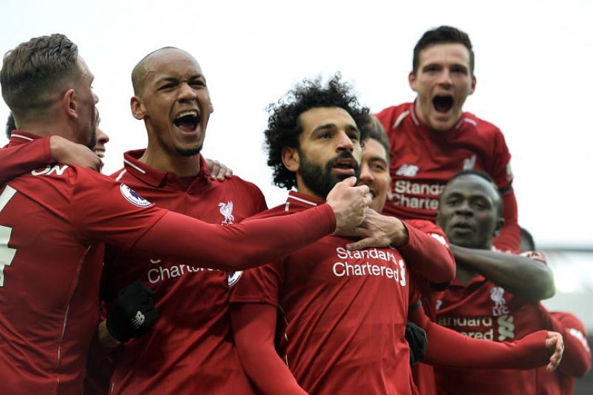 Liverpool's Mohamed Salah (centre) celebrates with teammates after scoring the 2-0 goal during the EPL match between Liverpool FC and Chelsea FC at Anfield, Liverpool, Britain, on April 14, 2019.