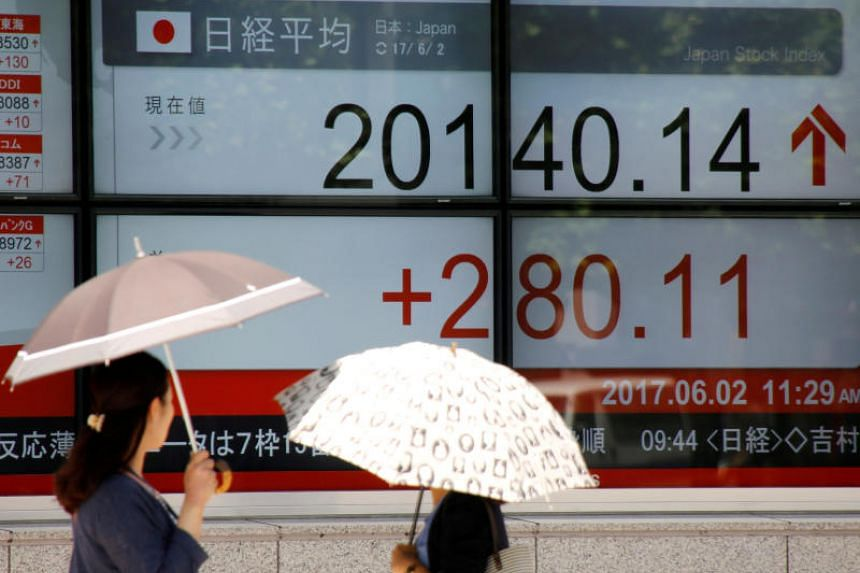 Passers-by look at an electronic board showing Japan's Nikkei average outside a brokerage in Tokyo, Japan June 2, 2017.