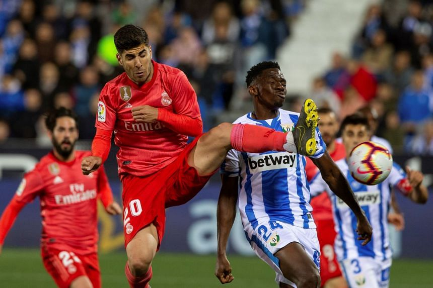 Real Madrid's Marco Asensio (left) in action against CD Leganes' Kenneth Omeruo (right).