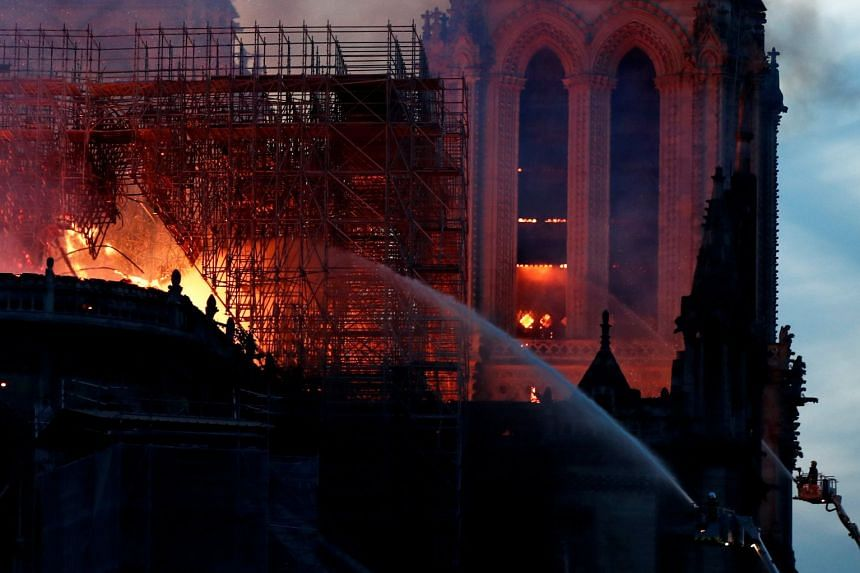 Firefighters dousing flames of the burning Notre Dame Cathedral.