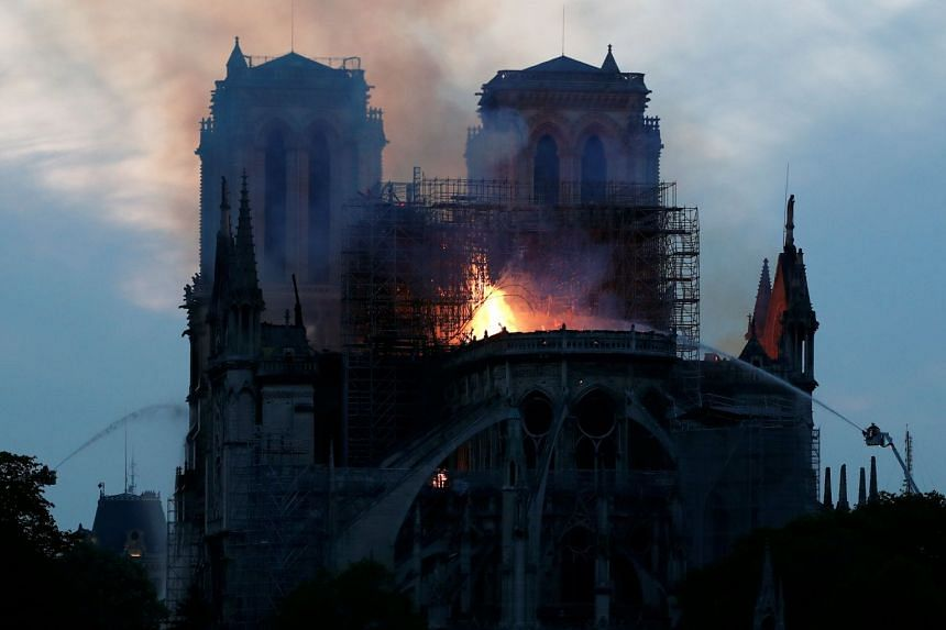 Firefighters dousing flames of the burning Notre Dame Cathedral in Paris.