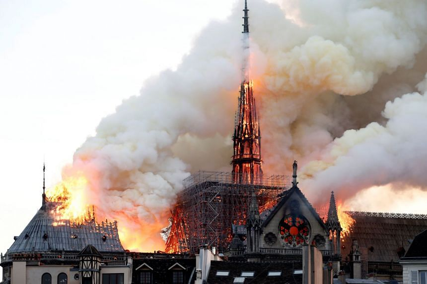 Smoke billows as fire engulfs the spire of Notre Dame Cathedral in Paris.