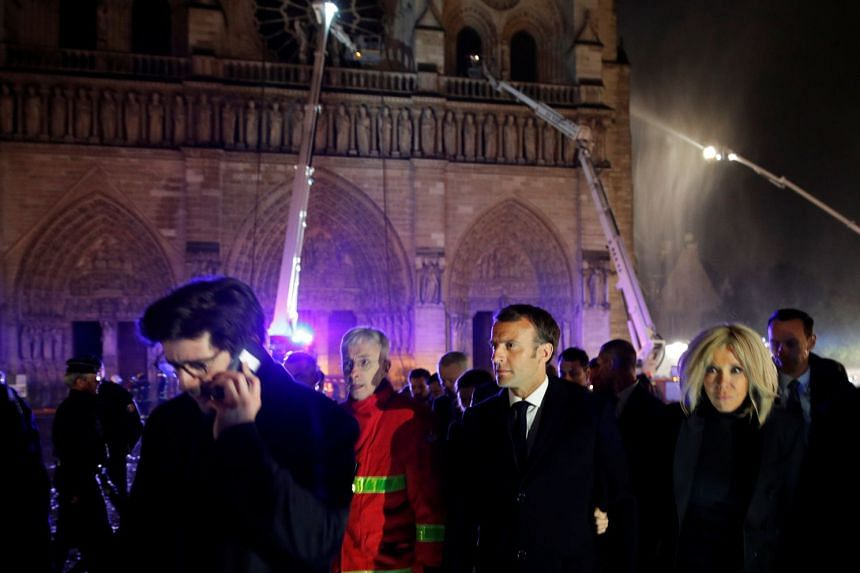 Macron and his wife Brigitte walk outside Notre Dame Cathedral as the fire continues to burn.