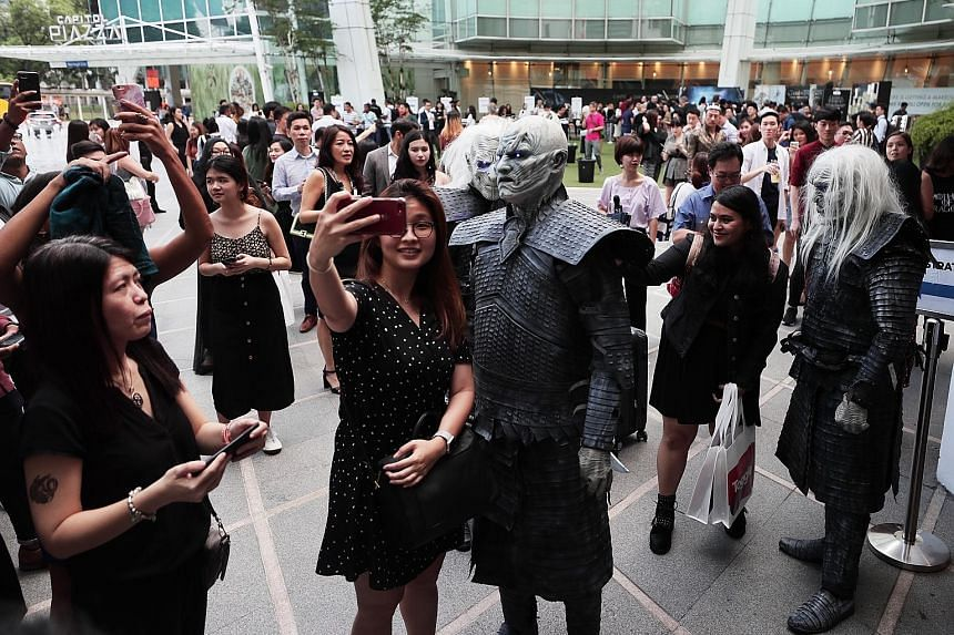 Above: The queue outside Capitol Theatre yesterday evening for the premiere screening of the first episode of the Game of Thrones' final season. Left: A fan taking a wefie with the Night King (centre), while another snapped a wefie with a White Walke