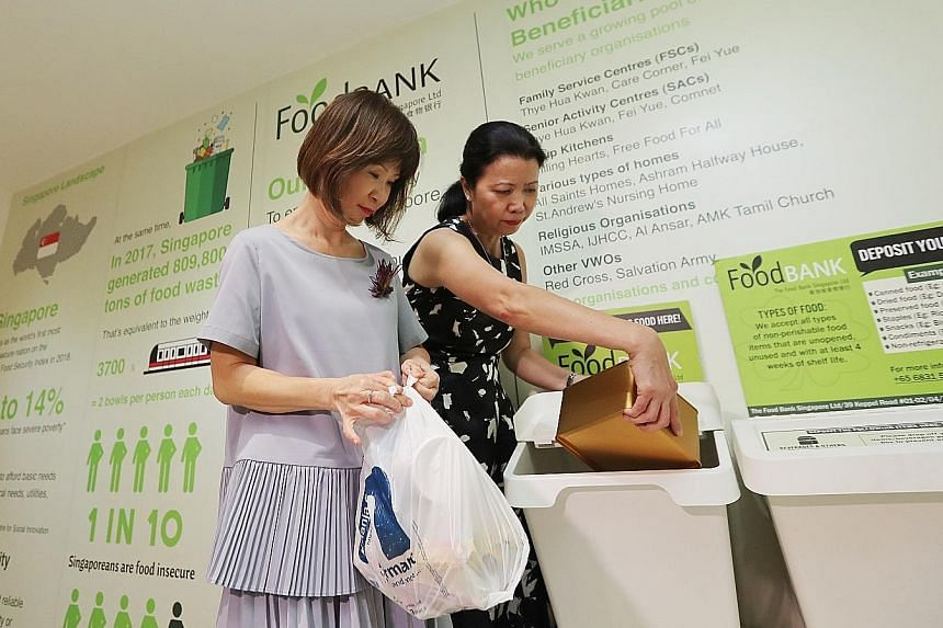 Senior Minister of State for the Environment and Water Resources Amy Khor (left) visiting the sustainability area at Compass One with the mall's centre general manager Sharon Tan yesterday.