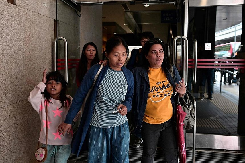 Philippine domestic worker Baby Jane Allas (centre), a single mother of five who was sacked by her employer after she was diagnosed with cancer, leaving with family members and supporters after a hearing at Hong Kong's labour tribunal yesterday. It o