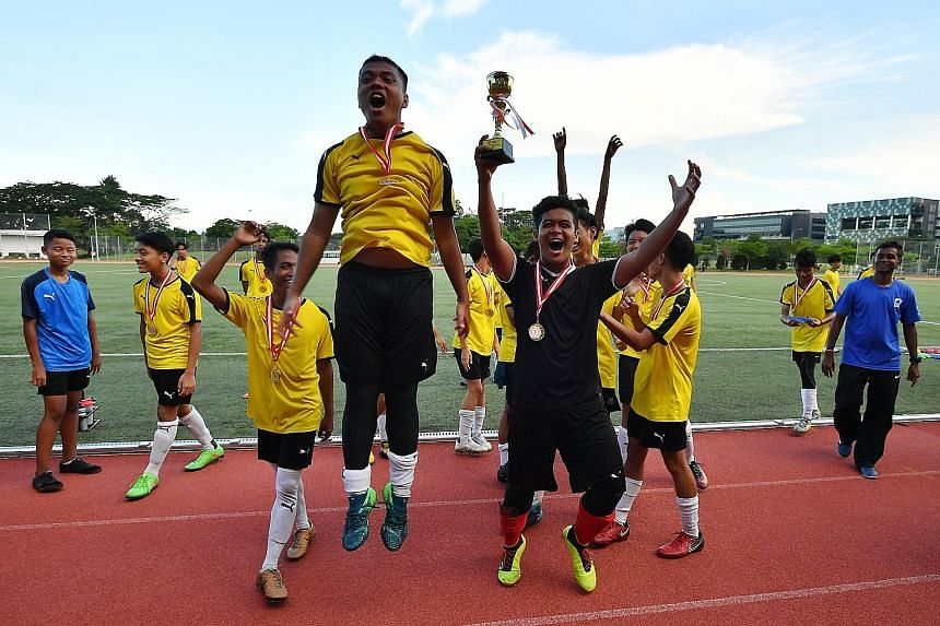 Above: Woodgrove Secondary player Shannel Saifudin (left) challenging Guangyang Secondary's Ashish Budha Magar for the ball. Left: Guangyang players celebrating with the trophy - their first B Division title.