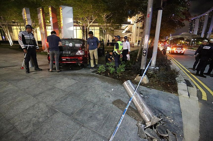 A car crashed into a metal bollard outside the Marina Bay Financial Centre yesterday evening. The 25-year-old driver has been arrested. PHOTO: LIANHE ZAOBAO