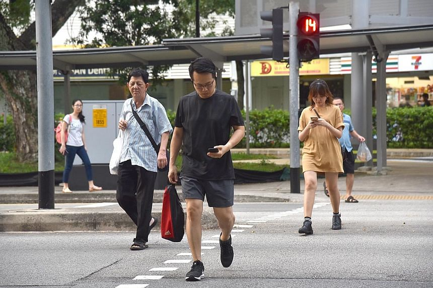 The pedestrian crossing at Block 177 Toa Payoh Central. Some have called for legislation to ban pedestrians crossing the road from using their mobile phones. The idea to fine errant pedestrians is not new. Such laws are already in place in selected A