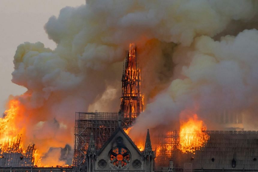Smoke billows as flames burn through the roof of the Notre-Dame de Paris Cathedral on April 15, 2019.  YouTube's software mistakenly labelled the plumes of smoke as footage from 2001, triggering the panel below the video.