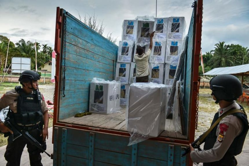 Indonesian police provide security as election workers transport ballot boxes to a polling station ahead of the April 17 elections in Trumon, Southern Aceh province, on April 15, 2019.