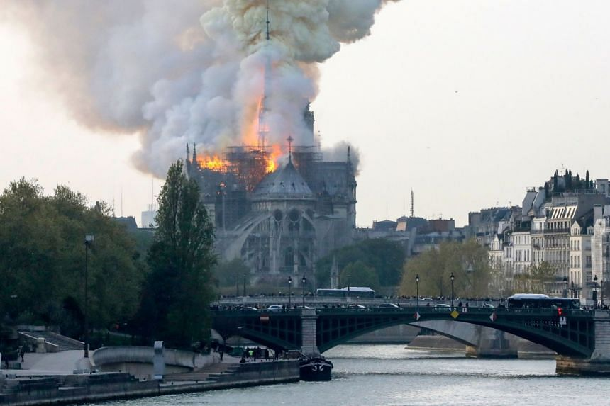 Smokes ascends as flames rise during a fire at the landmark Notre Dame Cathedral in central Paris.