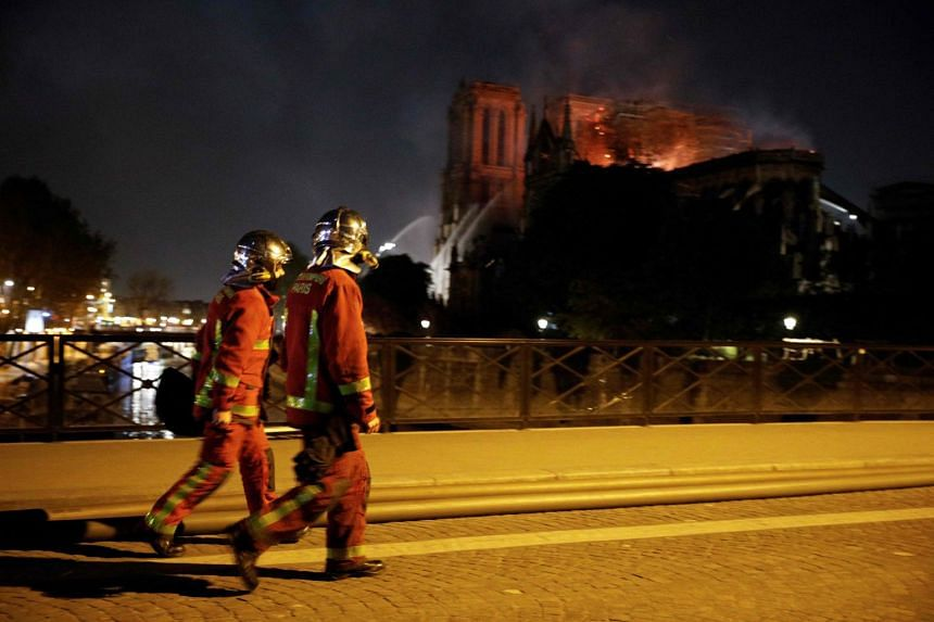 Firefighters look towards the fire at the landmark Notre Dame Cathedral in central Paris.