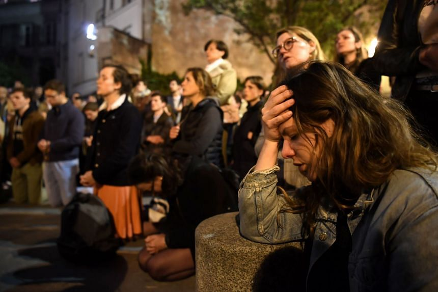 People kneel and pray as flames engulf Notre Dame Cathedral in Paris.