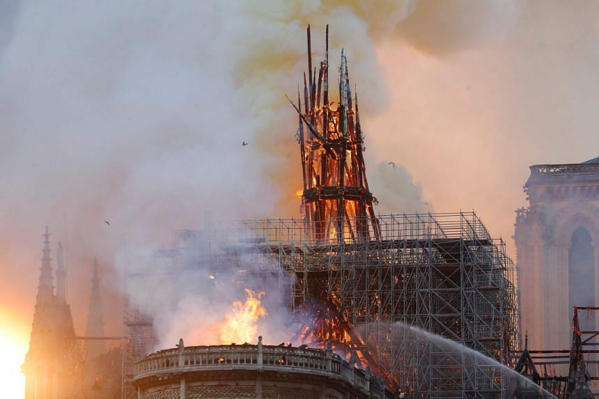 Smoke and flames rise during a fire at the landmark Notre Dame Cathedral in central Paris.