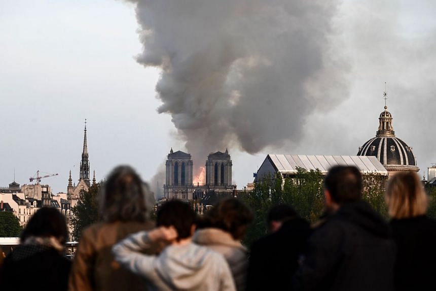People watch the landmark Notre Dame Cathedral burns in central Paris.