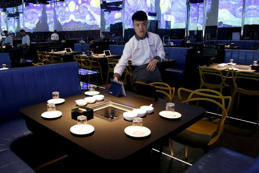 A waiter prepares a table for service at a Haidilao hotpot restaurant in Beijing.