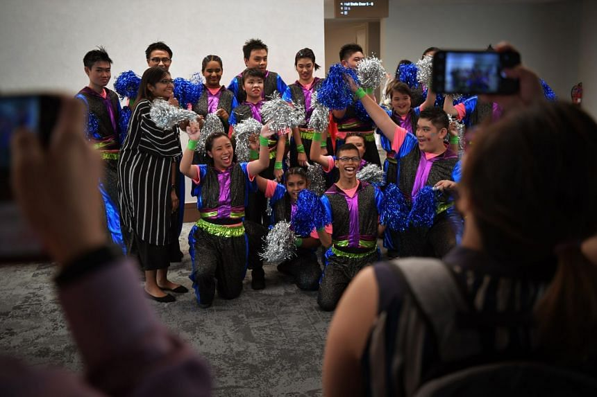 APSN Tanglin School students performing last Wednesday at the Singapore Youth Festival Arts Presentation held at the National University of Singapore, while students from APSN Delta Senior School (above) posed for photographs after their performance.