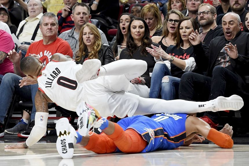 Portland's Damian Lillard is tripped by Oklahoma City's Russell Westbrook at Moda Centre in Oregon on Sunday. The Blazers won 104-99 - their first play-off victory since the 2015-16 season.