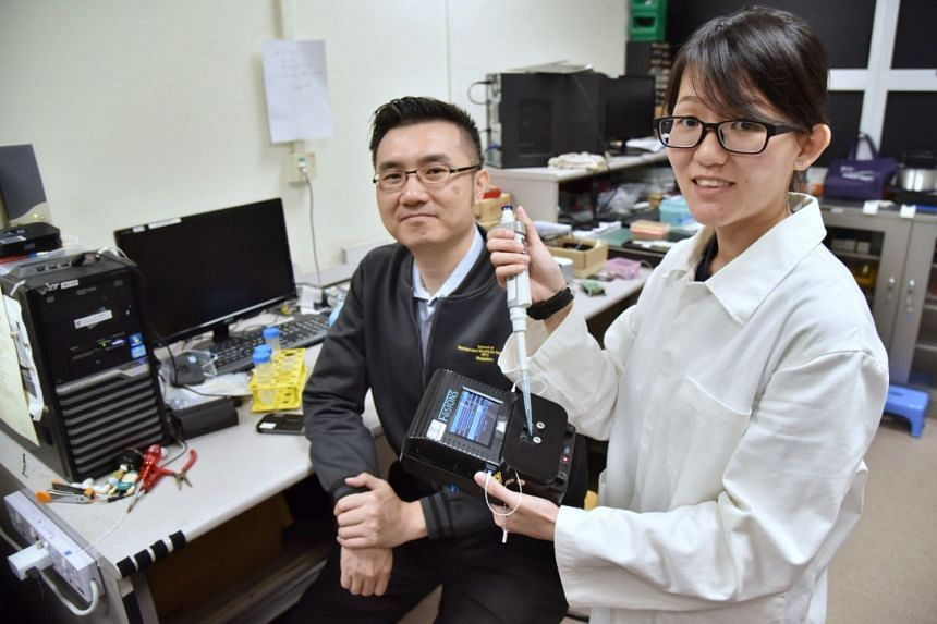 Prof Yong Ken-Tye with PhD student Stephanie Yap, who is holding a prototype of the device that can quickly detect trace levels of heavy metal contaminants in drinking water. It can identify 24 types of metal contaminants, double the number that comm