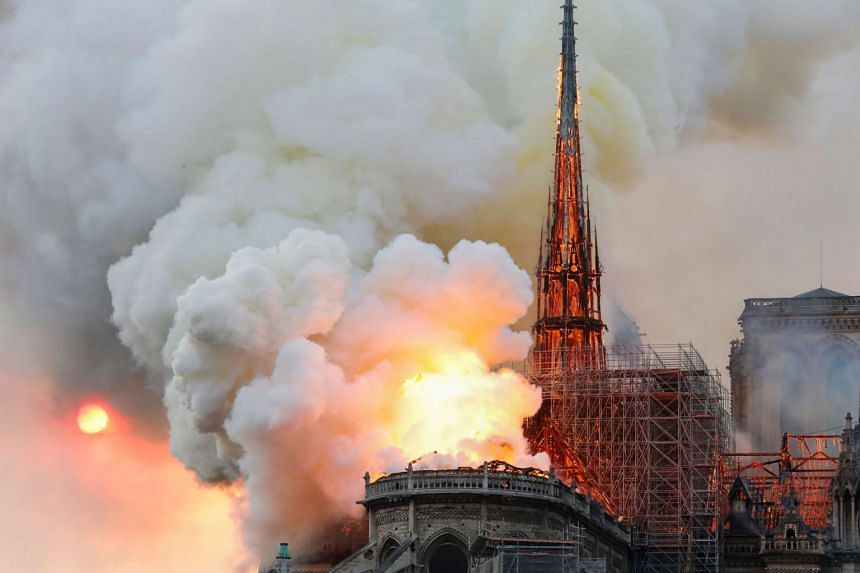 Smoke and flames rise during a fire at the landmark Notre Dame Cathedral, before the spire fell.