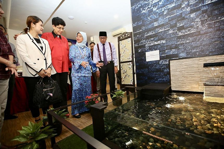President Halimah Yacob, flanked by Ain Society chief executive Mohamad Yusof Ismail and the society's medical adviser, Marine Parade GRC MP Fatimah Lateef, admiring a water feature in the society's new cancer centre yesterday at Block 9 Haig Road. A