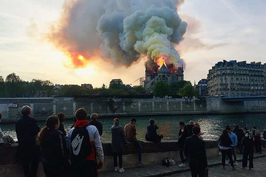 People watching in shock as smoke billowed from the top of the famed Notre-Dame Cathedral on Monday. French media reported that the fire may be linked to renovation work on the roof and the spire. PHOTO: AGENCE FRANCE-PRESSE Above: A woman overwhelme