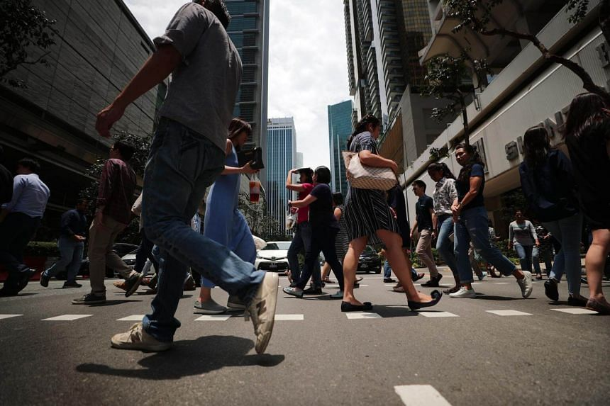 A lunch crowd crossing the road at Singapore's central business district, on March 29, 2019.