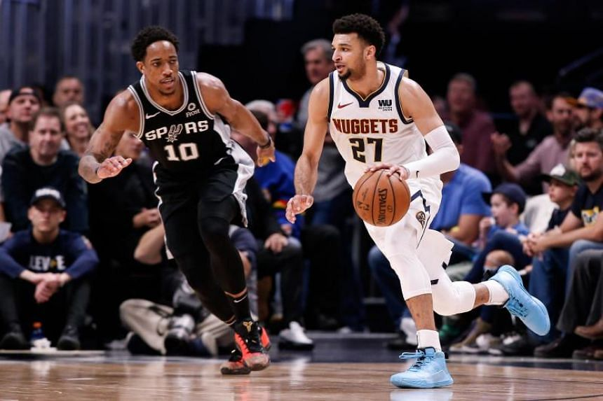 Denver Nuggets guard Jamal Murray (in white) controls the ball as San Antonio Spurs guard DeMar DeRozan defends during the Western Conference first-round NBA playoffs at the Pepsi Center on April 16, 2019.