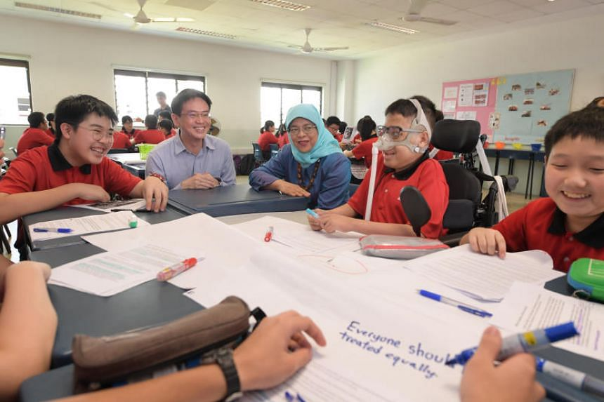 President Halimah Yacob with Zhenghua Secondary School students Muhammad Aaron Irwan (second from right) and Leroy Lim (left) and principal Eugene Lin during President Halimah's community engagement visit to the school on April 17, 2019.