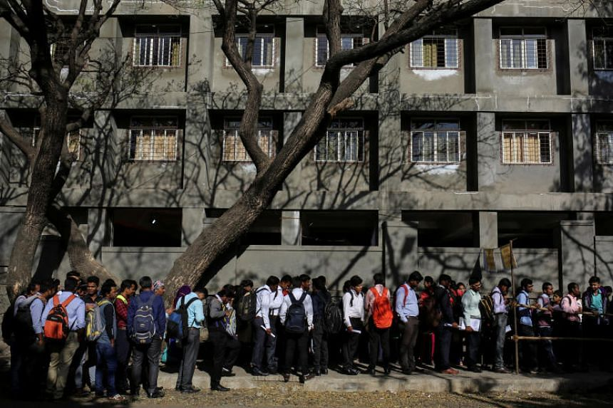 Jobseekers line up outside the venue of a job fair in Chinchwad, India, on Feb 7, 2019.