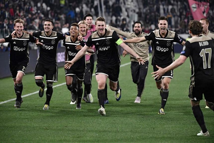 Ajax's Dutch midfielder Frenkie de Jong (left), Ajax's Dutch defender Matthijs de Ligt (centre) and teammates celebrate after defeating Juventus during the UEFA Champions League quarter-final second leg football match at the Juventus stadium in Turin