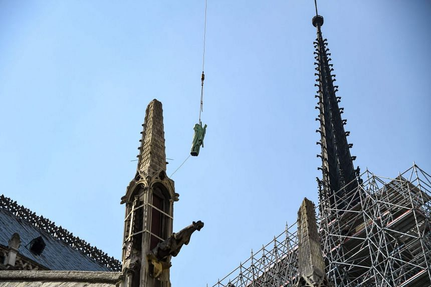 A crane lifts one of 16 copper statues in front of the Cathedral steeple and spire on April 11, 2019.