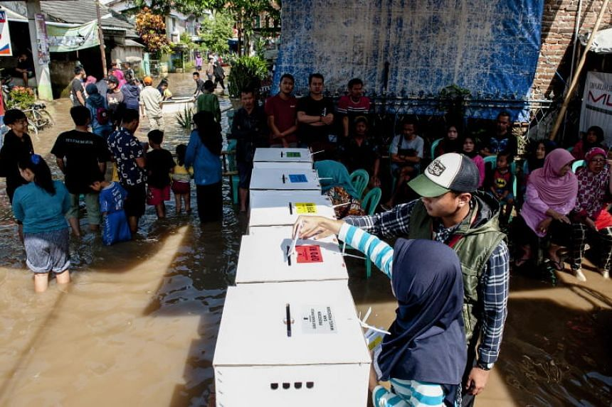 An Indonesian woman casts her ballot during the general election at a flooded polling station in Bandung, West Java.