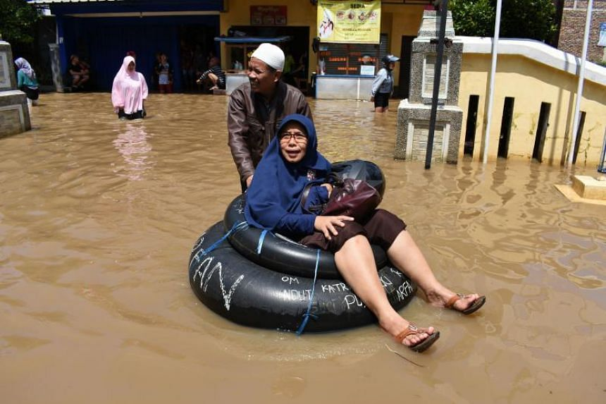 An Indonesian woman commuting through a flooded area to a polling station in Bandung, West Java.