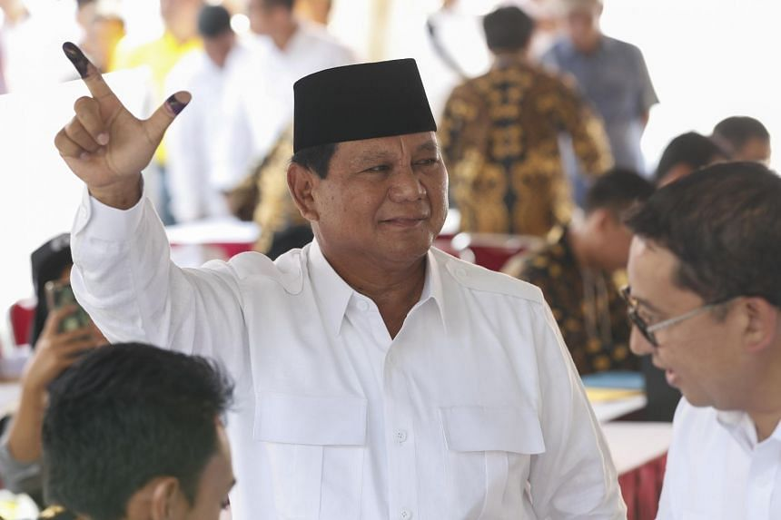 Prabowo Subianto displays his finger marked with ink to his supporters at a polling centre at Bojong Koneng Village in Bogor, Indonesia, on April 17, 2019.