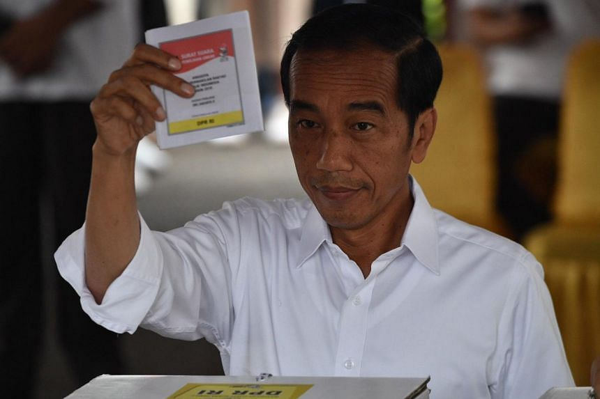 Indonesian president Joko Widodo casting his vote at a polling station in Jakarta, on April 17, 2019.