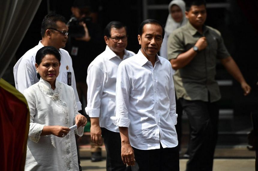 Indonesian president Joko Widodo and his wife arriving to cast their votes at a polling station in Jakarta, on April 17, 2019.
