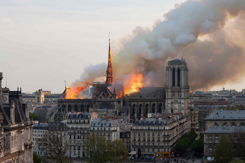Smoke billows as flames burn through the roof of the Notre-Dame Cathedral in Paris on April 15, 2019.