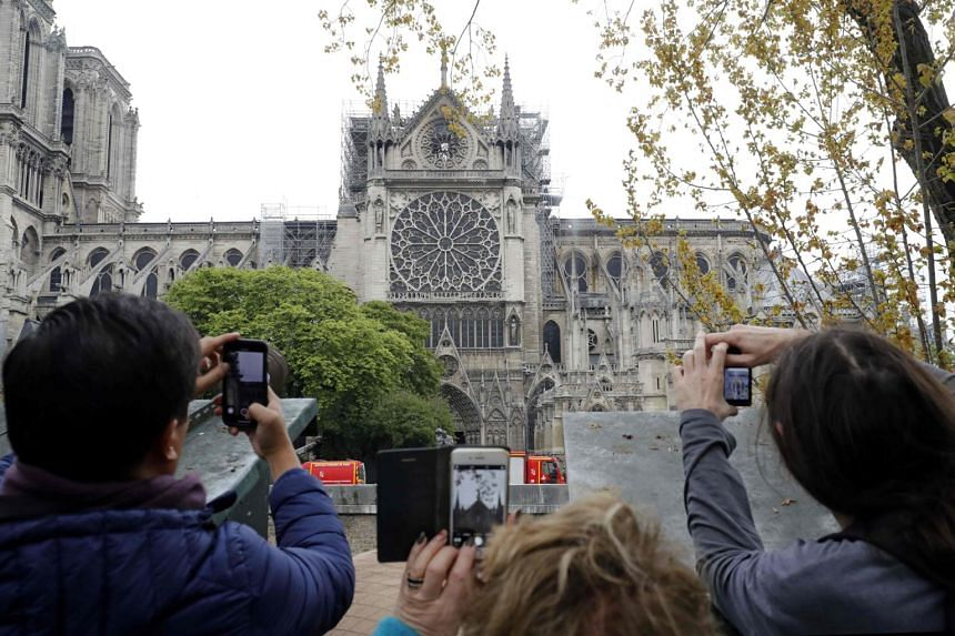 People take pictures of Notre-Dame Cathedral a day after a fire devastated the building in central Paris, on April 16, 2019.