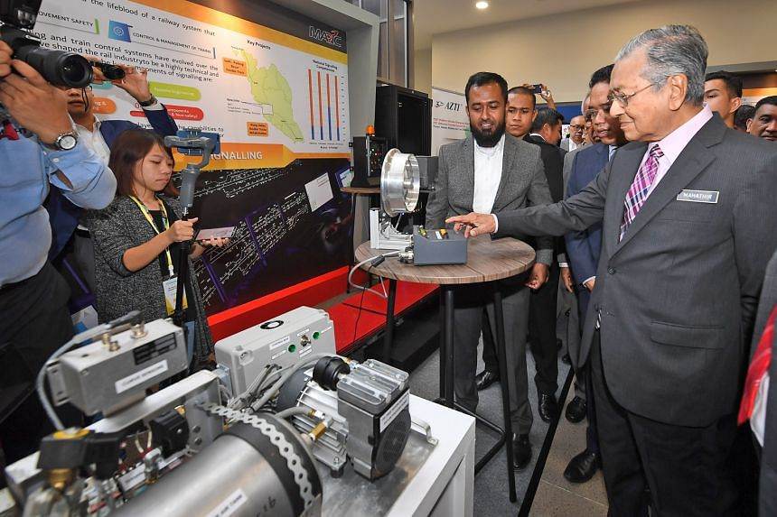 Malaysian Prime Minister Mahathir Mohamad visiting a technology exhibition in Cyberjaya yesterday. He said that a high-speed train between Singapore and Kuala Lumpur would benefit only a few states between the two cities. PHOTO: BERNAMA