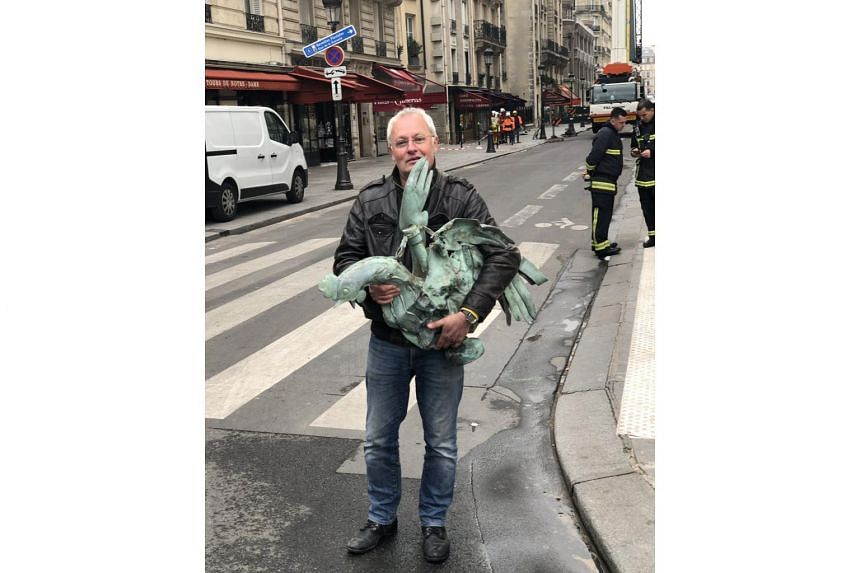 The head of the French Builders Federation, Jacques Chanut, posted a picture of a restorer holding a green-coloured rooster statue in the street.